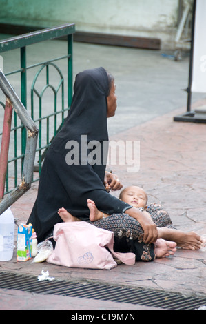 A woman and her baby begging in Bangkok, Thailand Stock Photo