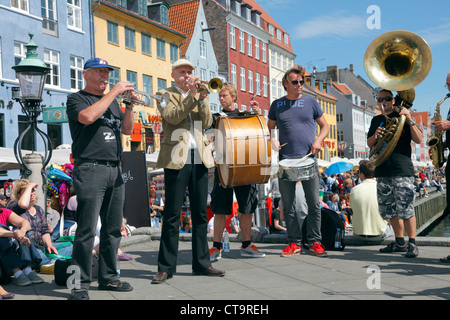The Orion Brass Band in Nyhavn on a sunny summer day crowded with jazz fans and tourists having a beer or taking - Stock Photo