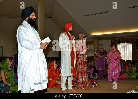 Traditional East Indian wedding Holy Man groom bride wedding guest seated cross legged on floor Sikh temple - Stock Photo