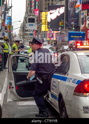 Answering a call, a policeman hurries from his squad car in Times Square, New York City. Note police mobile guard - Stock Photo