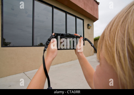 Six--year-old girl uses a digital camera to photography the windows of a shopping mall commercial building in Mission - Stock Photo