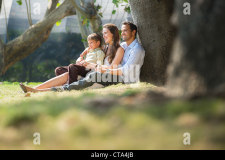 Happy family with man, woman and child leaning on tree in city park. Copy space - Stock Photo