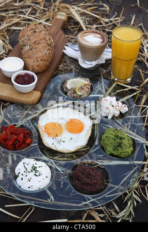 Traditional Israeli Breakfast with two fried eggs, cheeses, salads, fresh bread, orange juice and a cup of cappuccino - Stock Photo