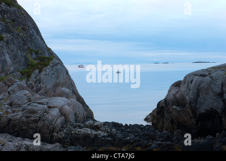 View towards the sea with fishing boats and rocky landscape in the morning light, Austvagoy, Lofoten, Nordland, - Stock Photo