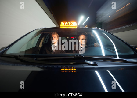Taxi driver and passenger inside a cab, driving at high speed at night - Stock Photo