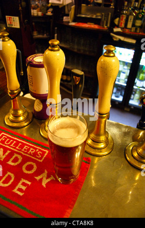 A pint of ale, beer on the bar at the The Grenadier pub, Wilton Row, Belgravia, London, at dusk, pub table drinks - Stock Photo