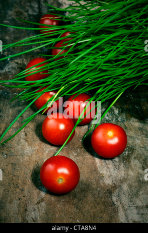 salad tomatoes in rustic setting - Stock Photo