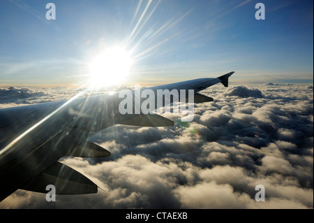 Sun above clouds with wing of airplane, flight from Delhi to Leh, Ladakh, Jammu and Kashmir, India - Stock Photo