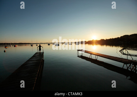 Child on a wooden jetty at sunset, Lake Woerthsee, Starnberg, Upper Bavaria, Bavaria, Germany - Stock Photo