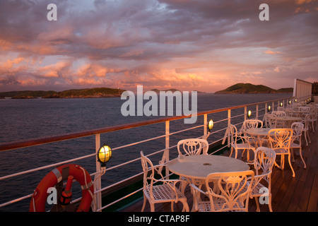 Tables and chairs on deck of cruise ship MS Deutschland, Reederei Peter Deilmann, with storm clouds at sunset, Cabo - Stock Photo