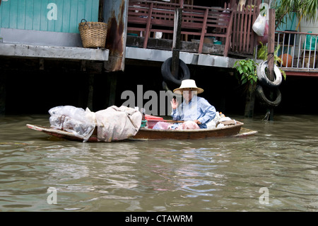 A Thai woman paddles her boat on the Bangkok Yai canal in Bangkok, Thailand - Stock Photo