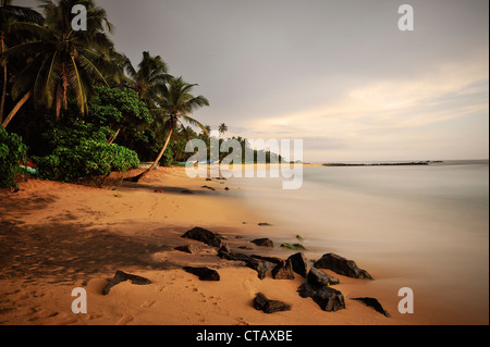 sunset at a bay around Mirissa beach, fishing boats between palm trees, Sri Lanka, Indian Ocean - Stock Photo