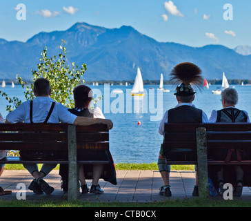 Couples wearing traditional clothes sitting on benches near harbor at lake Chiemsee, Prien, Chiemgau, Upper Bavaria, - Stock Photo