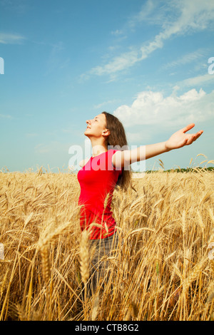 Teen girl staying at a wheat field with her arms outstretched - Stock Photo