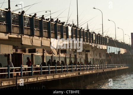 Galata bridge over Golden Horn with anglers, Istanbul, Turkey - Stock Photo