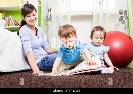 little toddler twins playing in the child's room - Stock Photo