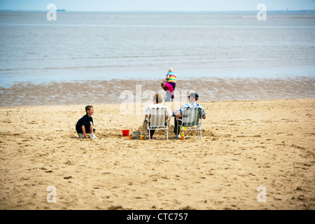 Family enjoying weather on Cleethorpes beach coast sat in deck chairs while kids play in sand - Stock Photo
