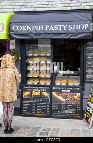 Cornish pasty shop with woman in a leopard skin coat looking at prices - Stock Photo