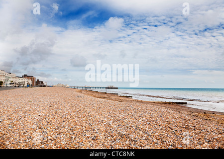 Wide shot of Worthing beach at low tide, with the Victorian pier in the distance - Stock Photo