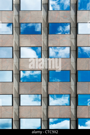 Blue sky and clouds reflected in Office block glass windows. London - Stock Photo