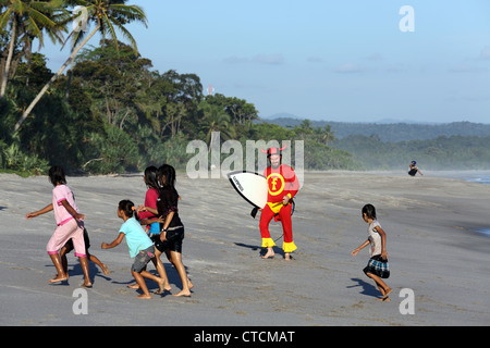 Strange surfing man with surfboard in a red superhero suit, scares children off a tropical beach in Sumatra, Indonesia. - Stock Photo