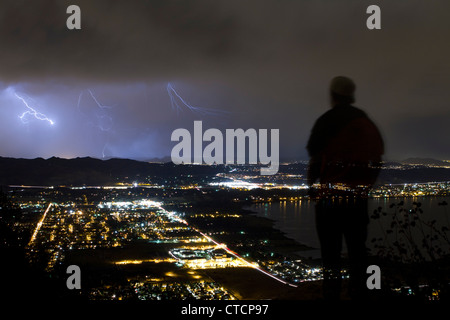 Silhouette of a young man watching a lighting storm over lake elsinore - Stock Photo