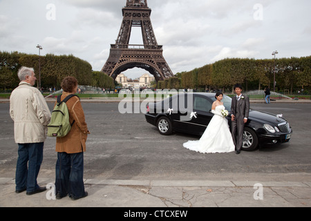 Foreign tourist look at a Chinese couple posing to wedding photos in the Field of Mars near Eiffel Tower in Paris, - Stock Photo