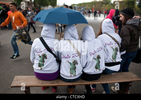 Foreign young tourists underneath the tower Eiffel Tower in Paris, France. - Stock Photo