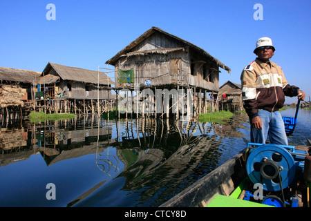 Burmese boatman driving through floating village, Inle lake, Shan state, Myanmar, Southeast Asia - Stock Photo