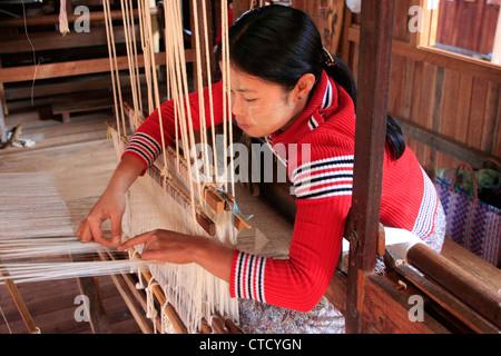 Young burmese woman weaving on a loam, Inle lake, Shan state, Myanmar, Southeast Asia - Stock Photo