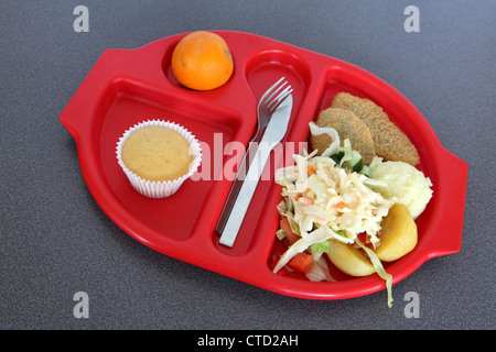 Healthy school lunch dinner served on preformed red plastic tray, salad bean burger, muffin, orange - Stock Photo