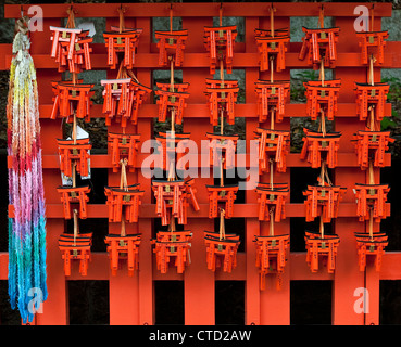 The Shinto shrine of Fushimi Inari-taisha, Kyoto, Japan. Miniature votive torii gates left as offerings by pilgrims - Stock Photo