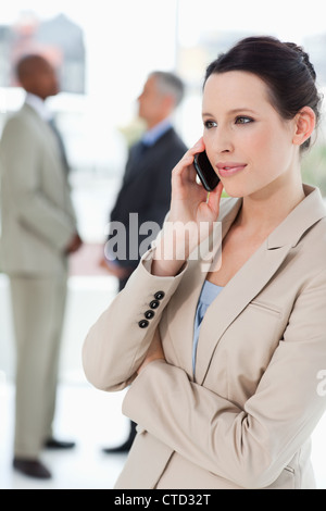 Businesswoman seriously talking on the phone with executives behind her - Stock Photo
