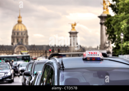 Parisian taxi illuminated sign on the car roof and Les Invalides on the background in Paris, France. - Stock Photo
