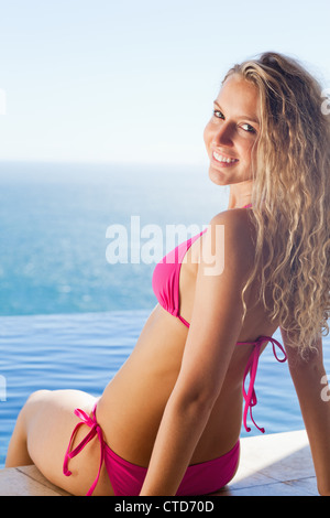Woman sitting at the pool edge with her head turned around - Stock Photo