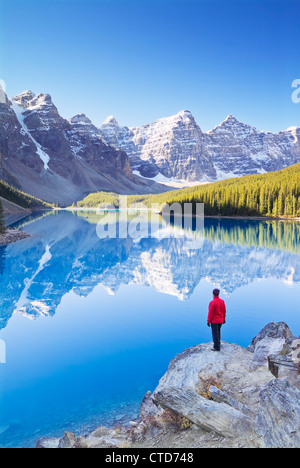 Tourist in red jacket looking at Moraine lake in the Valley of the Ten Peaks Banff national park Alberta Canada - Stock Photo
