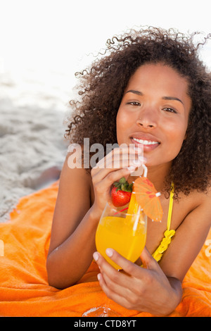 Young smiling woman holding an orange cocktail while looking at the camera - Stock Photo