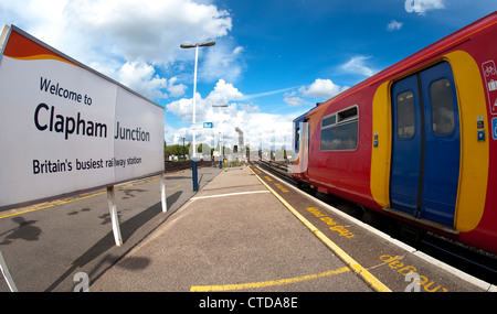 Welcome sign on the platform of Clapham Junction and train in South West Trains livery, England. - Stock Photo