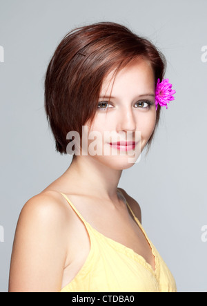 portrait of a beautiful teenage girl in yellow dress - isolated on gray - Stock Photo