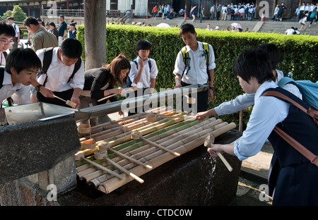 Todai-ji temple, Nara, Japan. Schoolchildren perform the ritual of temizu (purification) before entering the temple - Stock Photo