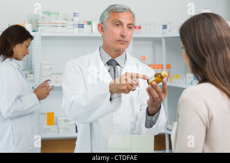 Pharmacist pointing at a flask of pills in front of a customer - Stock Photo