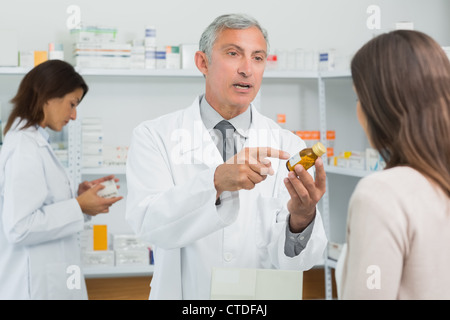 Pharmacist pointing a flask of pills in front of a customer - Stock Photo
