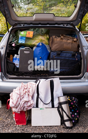 Family on vacation with their automobile packed with suitcases, bags, blankets and more - Stock Photo