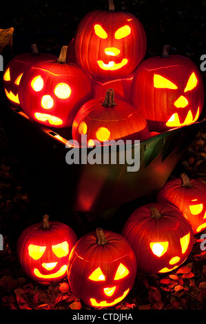 Lit carved pumpkins in a wheelbarrow with autumn leaves on backyard lawn at twilight. - Stock Photo