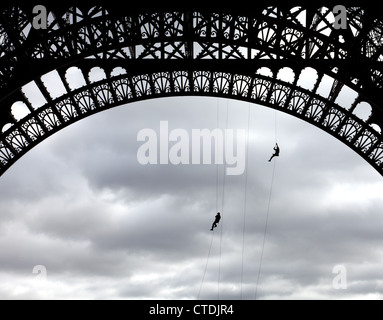 Paris, France: Paris firemen practice their skills from a base arch of the Eiffel Tower. - Stock Photo