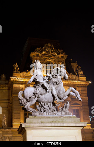 Statue of Louis XIV (Cour Napoleon du Louvre) by Bernini in the Louvre courtyard, illuminated at night. - Stock Photo