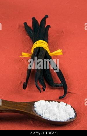 Vanilla pod and vanilla powder in a wooden spoon - Stock Photo