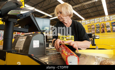 A senior female employee pensioner lady 70s working at the checkout counter in Jesse & Kelly's No Frills supermarket - Stock Photo