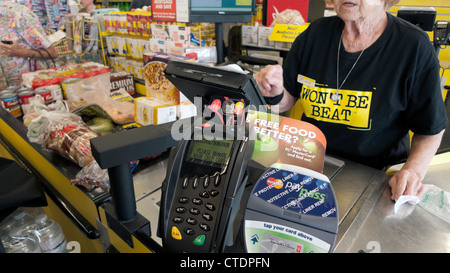 An elderly female employee older worker woman working behind the till checkout counter Jesse & Kelly's No Frills - Stock Photo