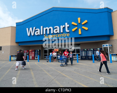 Exterior view of Walmart Supercentre Store and people with shopping trolley at the entrance of the store in Canada - Stock Photo